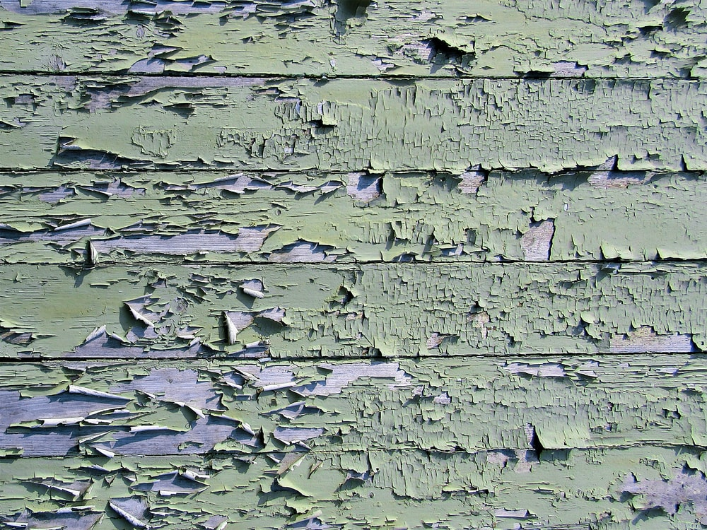 cracked green painting on wood plank
