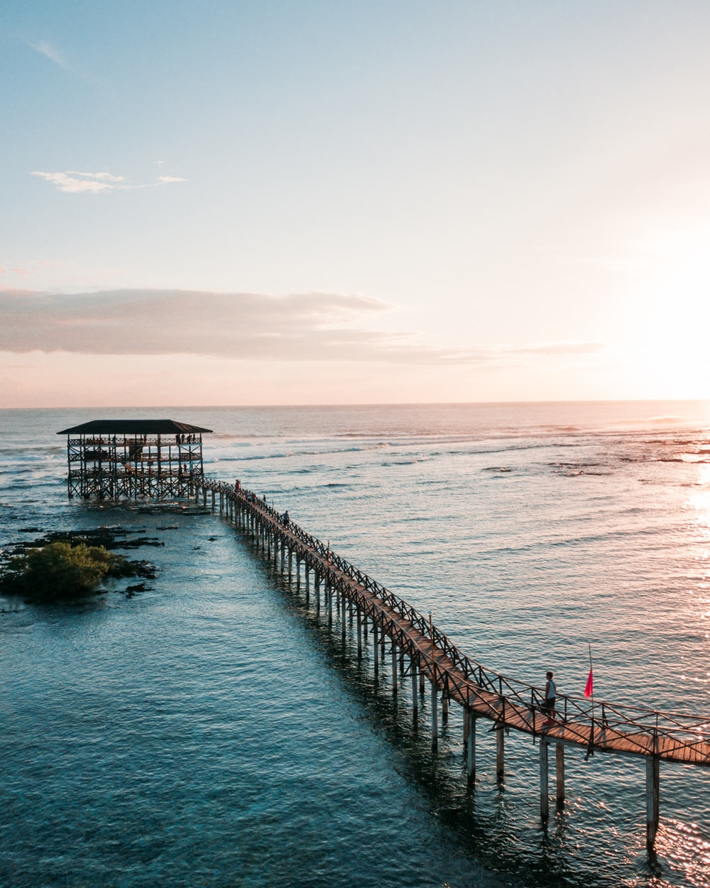 aerial photography of wooden foot bridge over blue sea