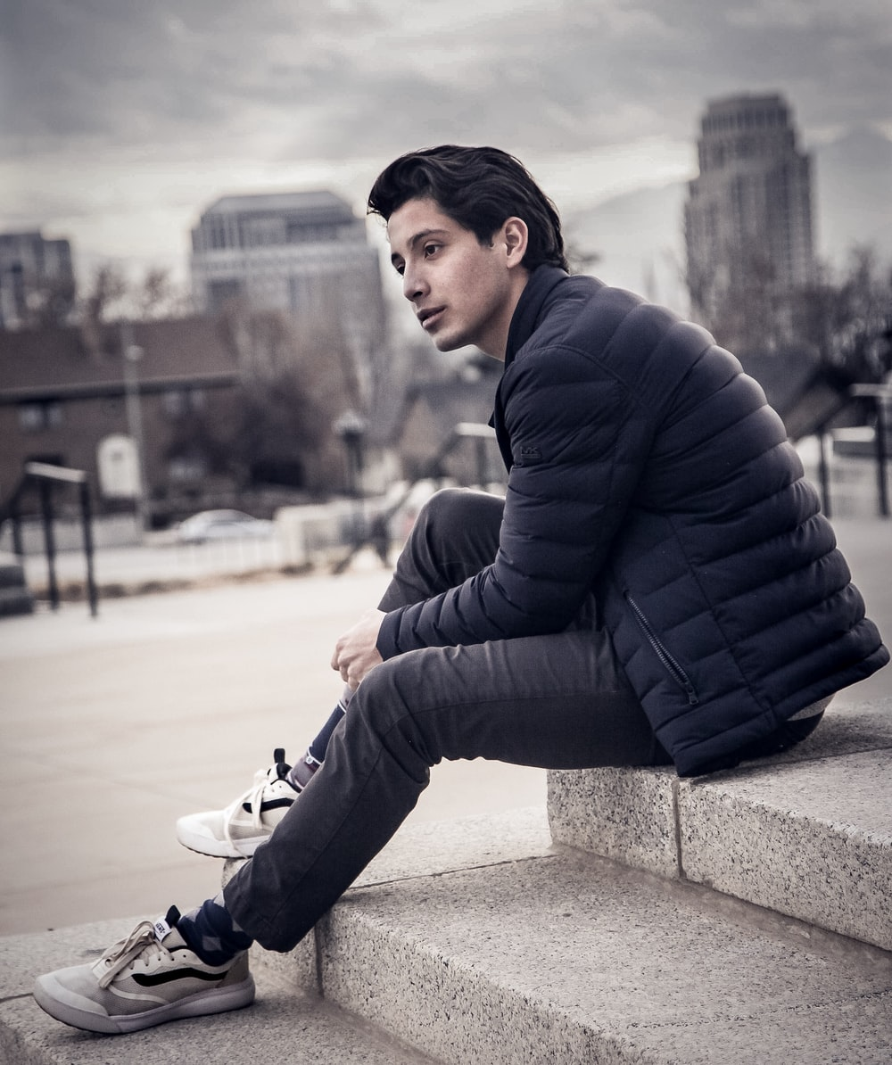 man sitting on concrete surface