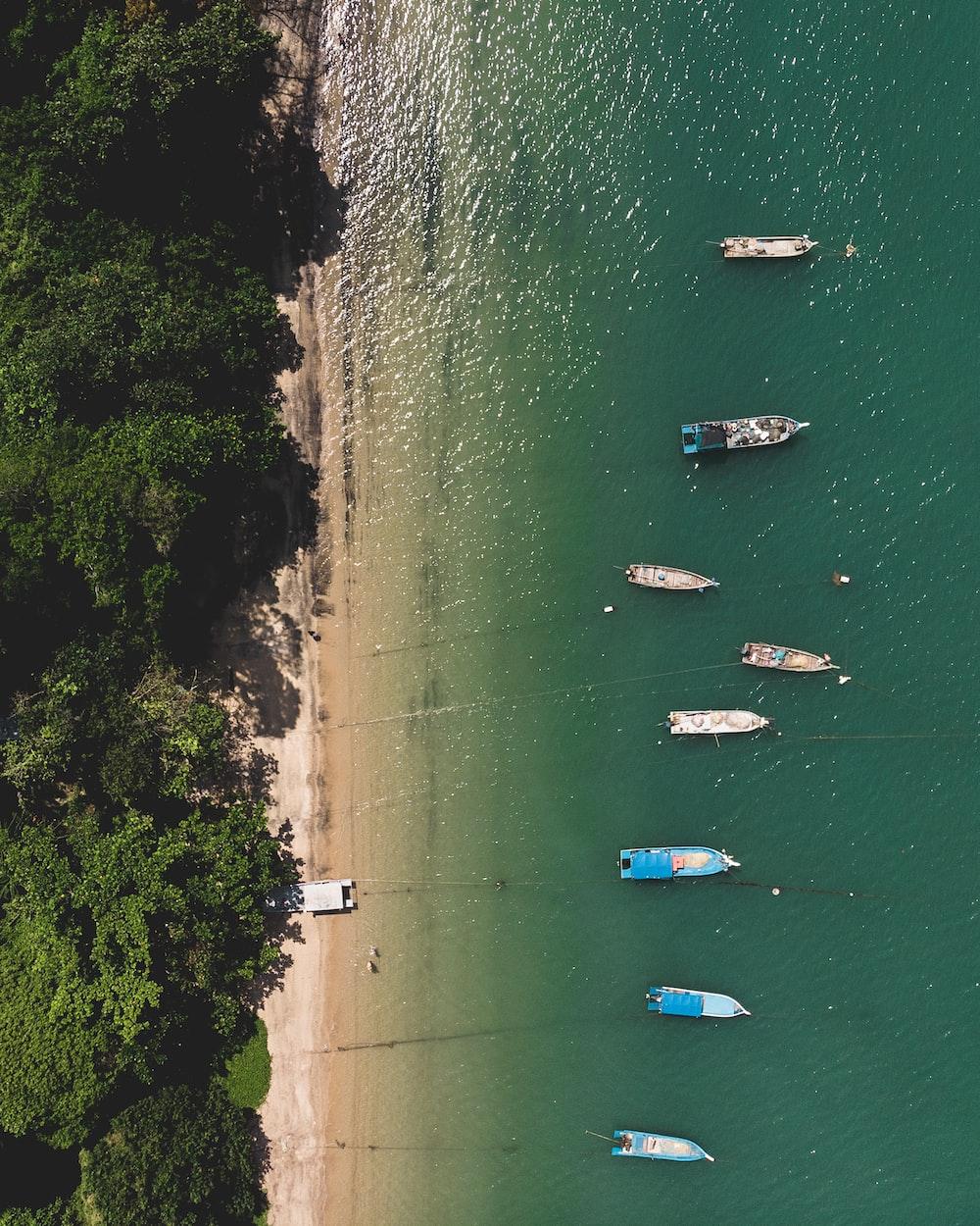 aerial photography of boats near white sand beachg