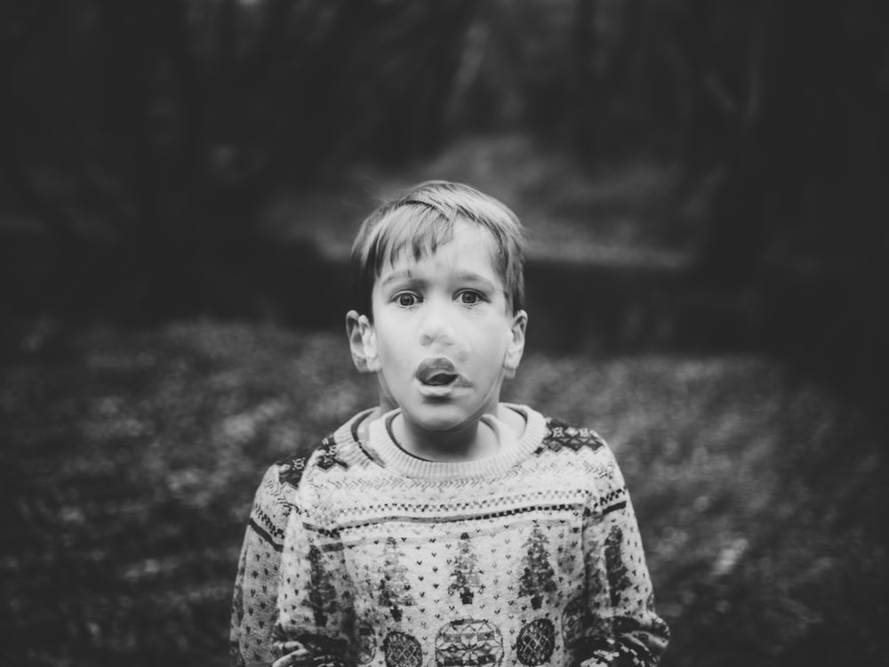 grayscale photography of boy wearing sweater