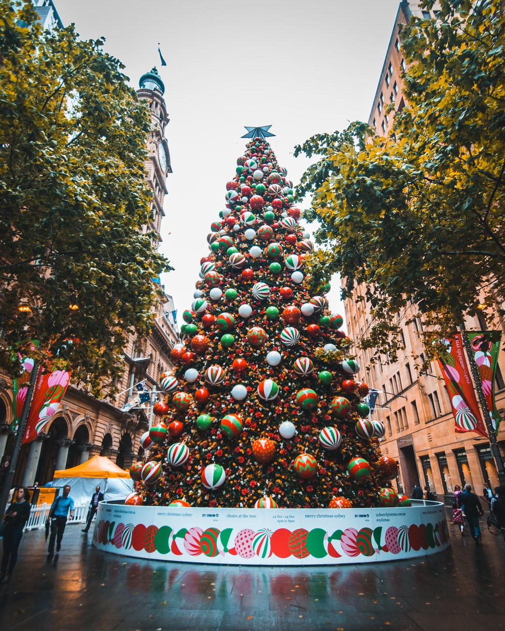 people walking beside Christmas baubles on large tree