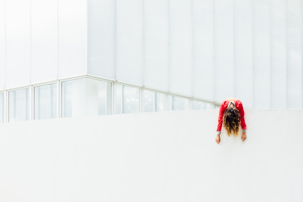 woman in red jacket on white painted concrete railings