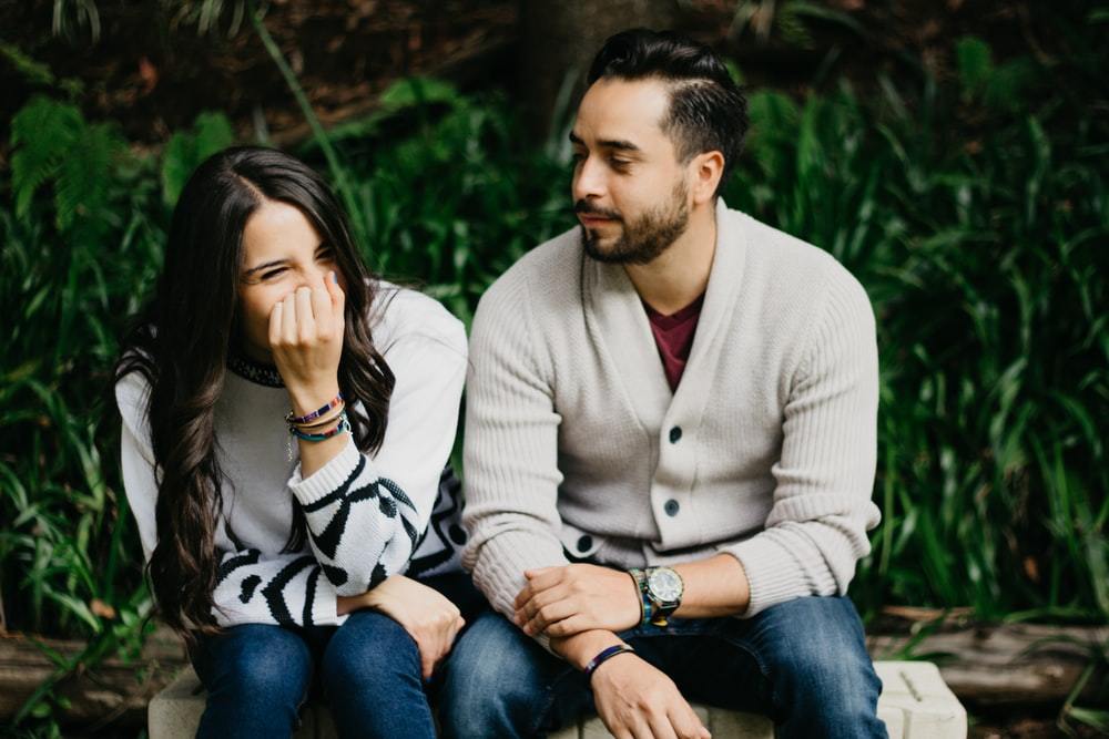 man sitting beside smiling woman