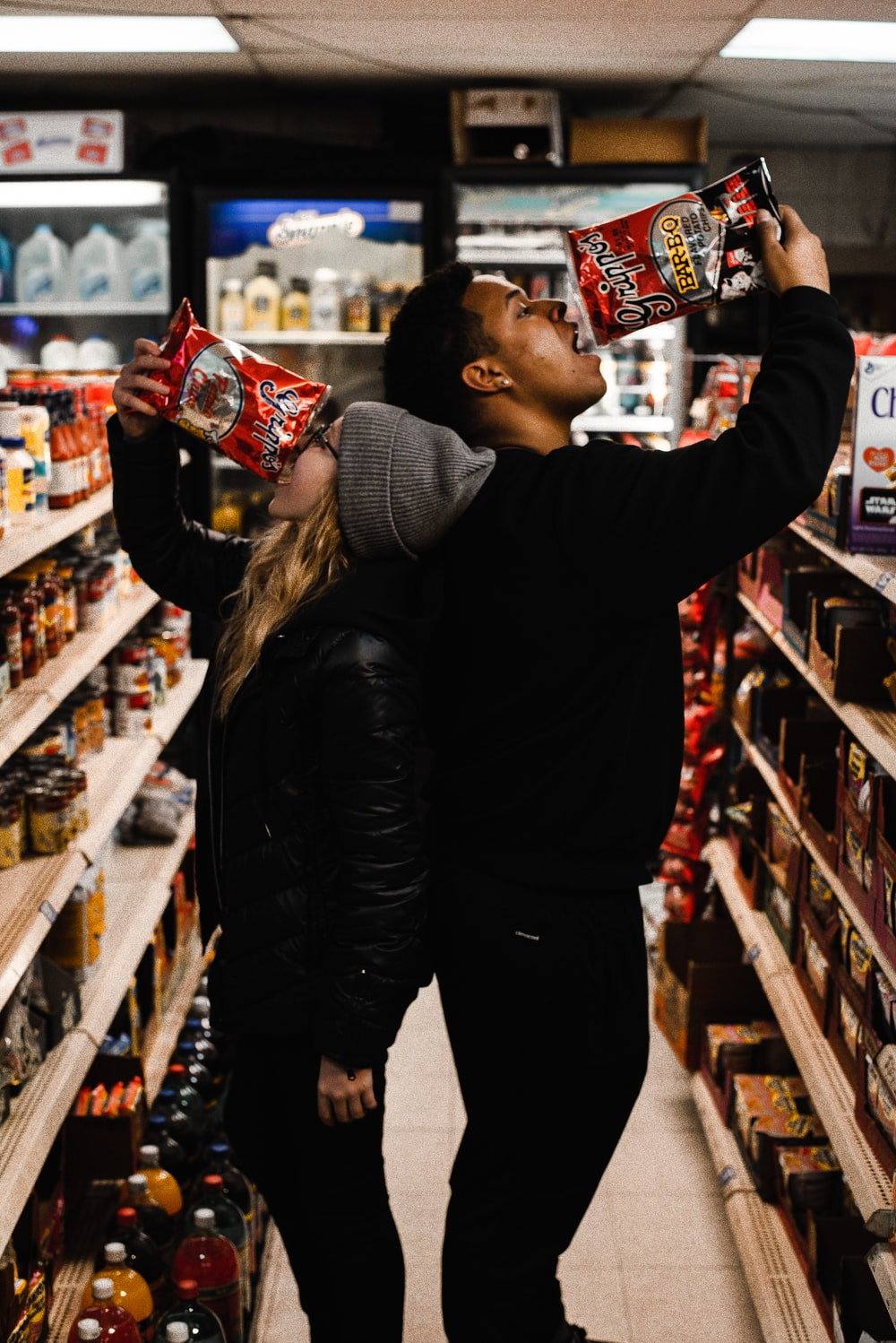 man and woman eating chips in shallow photo