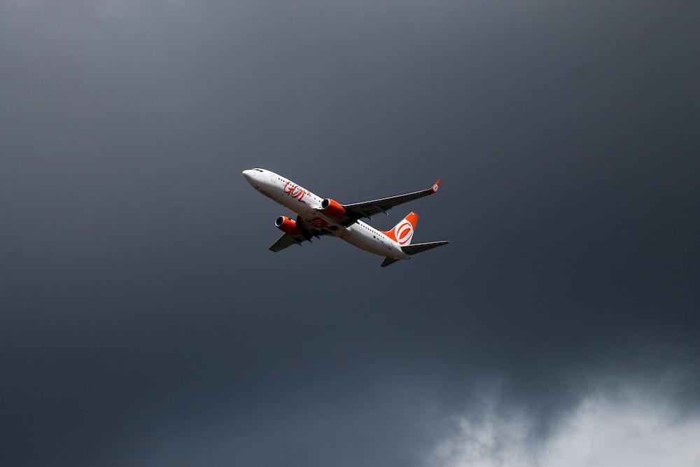 orange and white airliner on flight