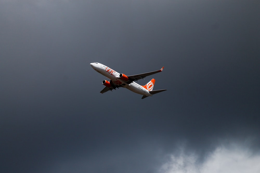 orange and white airliner on flight