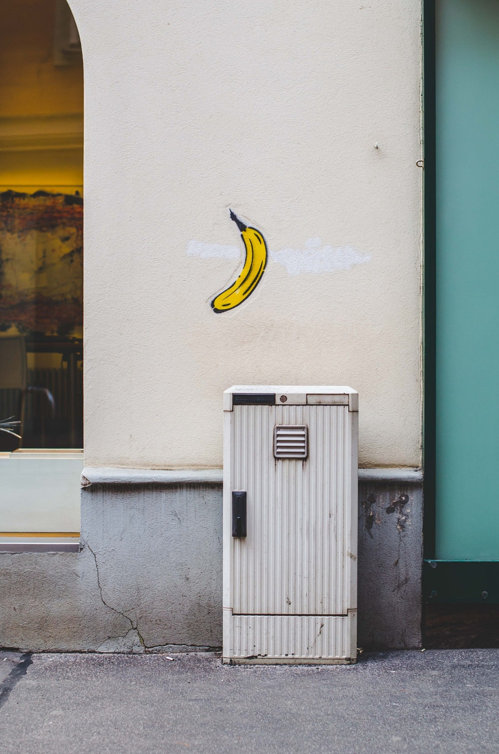 white mailbox near wall with banana fruit painting