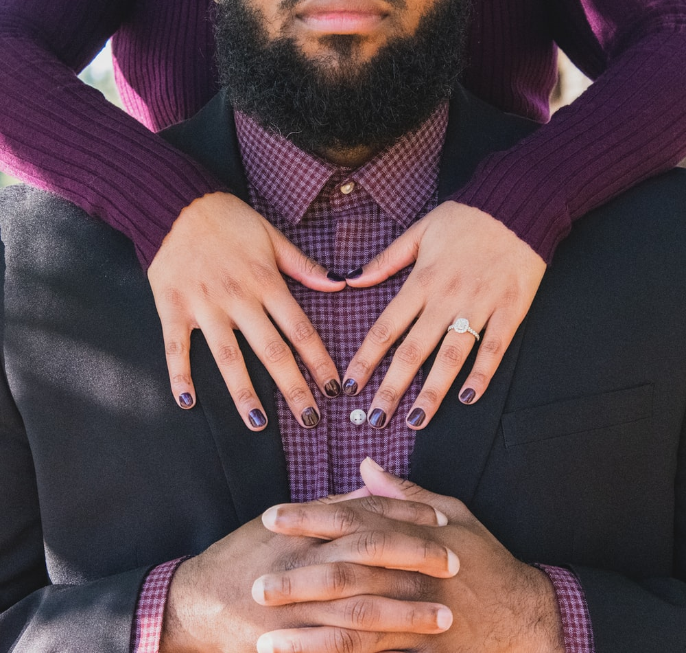 person standing at the back of man while touching his chest