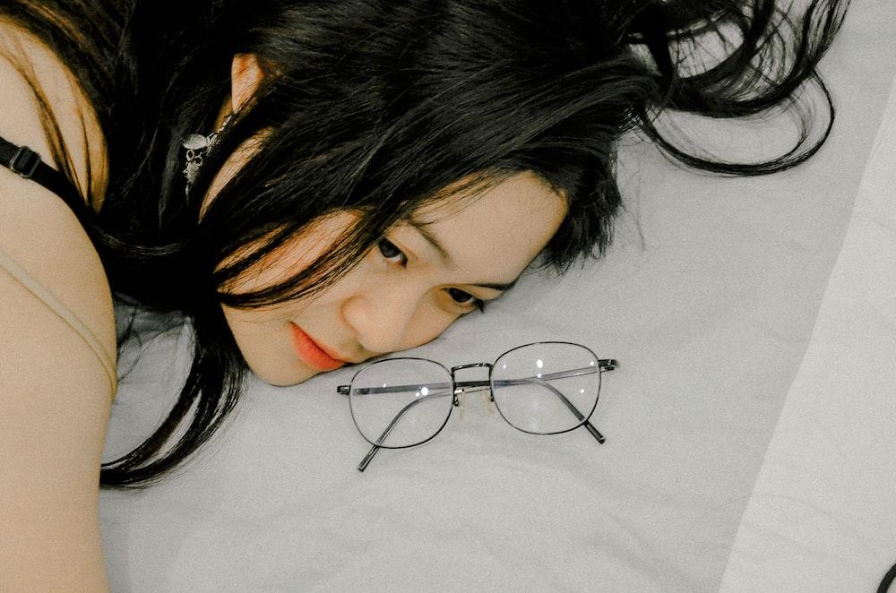 black frame eyeglasses near the woman lying on grey textile