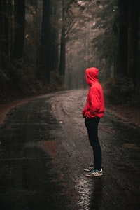 person standing in the middle of the road wearing hoodie
