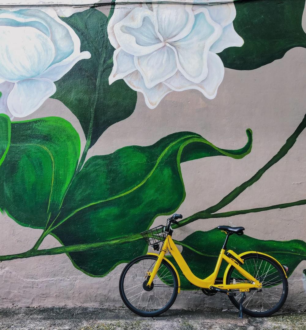yellow bike parked beside white flowers graffiti during daytime