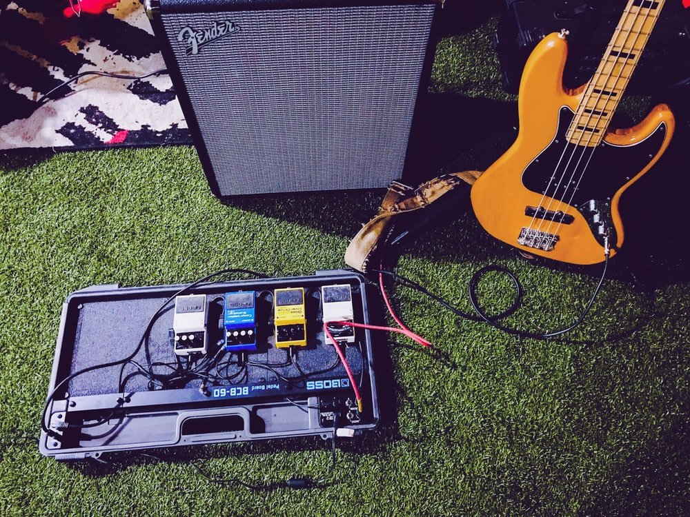 yellow electric bass guitar beside black Fender guitar amplifier
