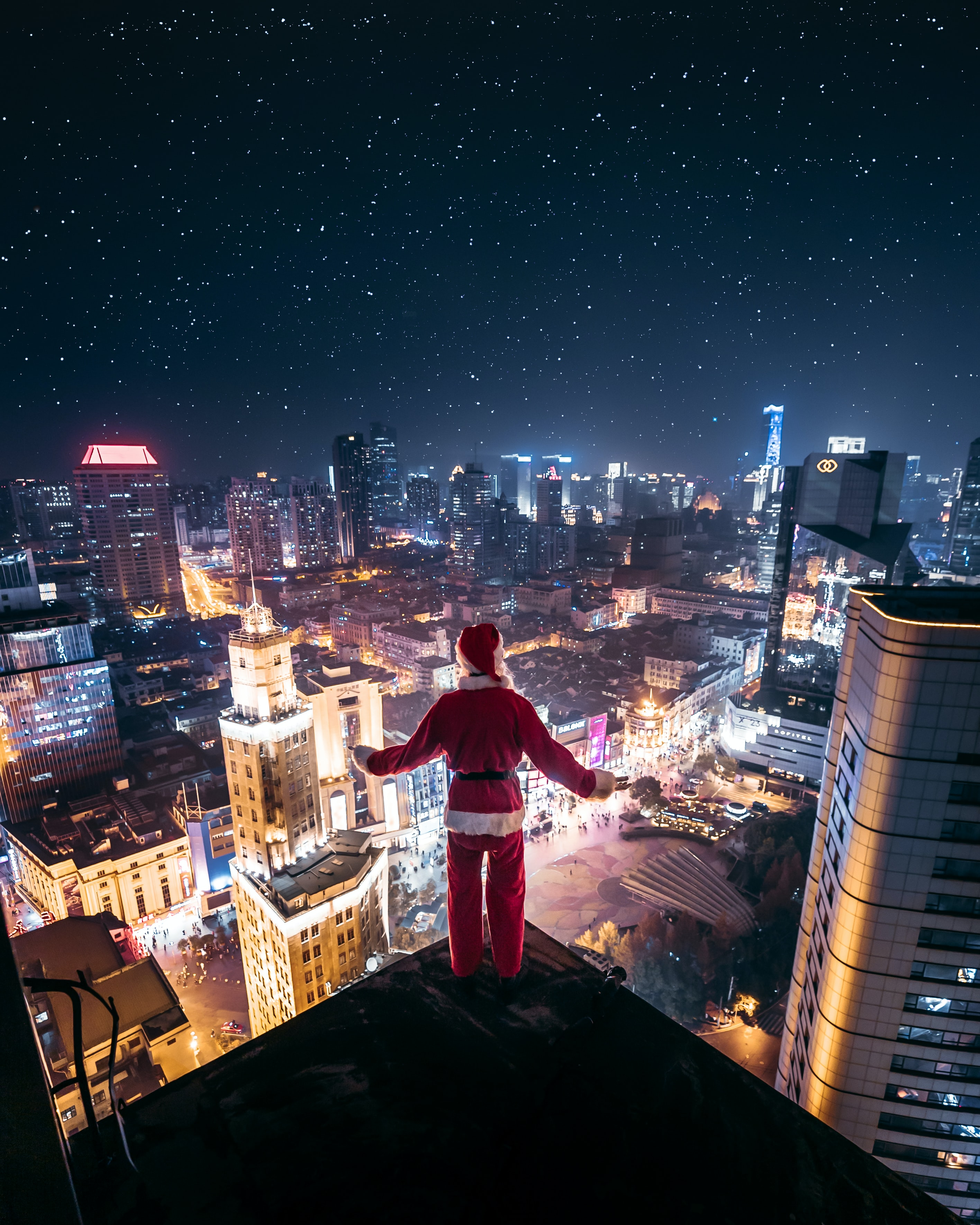 person wearing Santa Claus outfit standing on the edge of building at night time