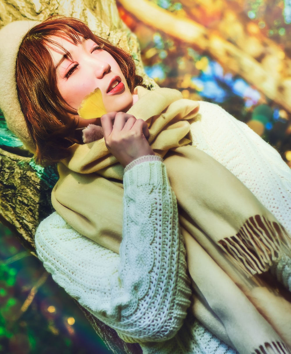 woman in white knit sweater holding yellow flower