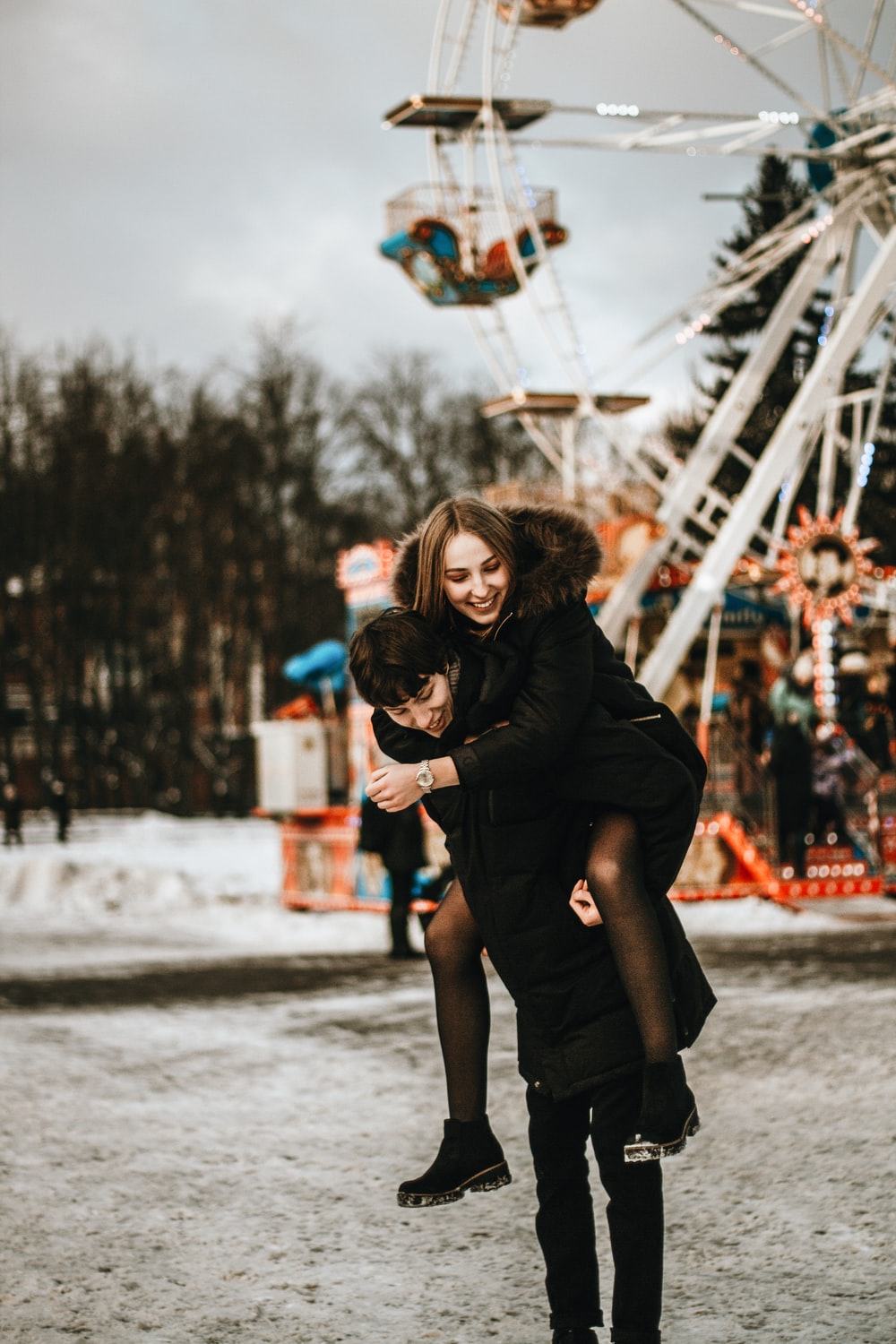 man carrying woman in front of ferris wheel