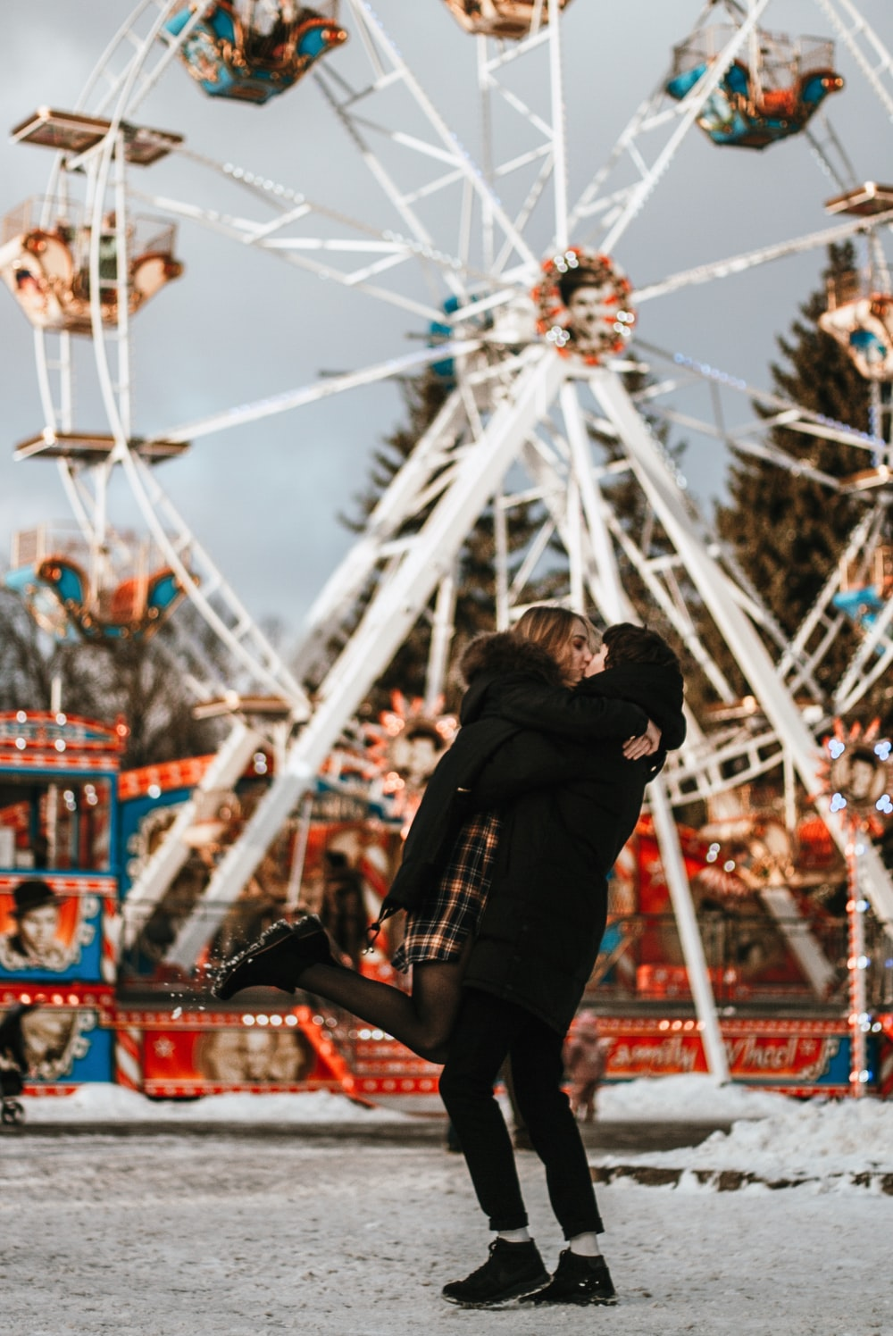 man and woman kissing near ferris wheel during daytime