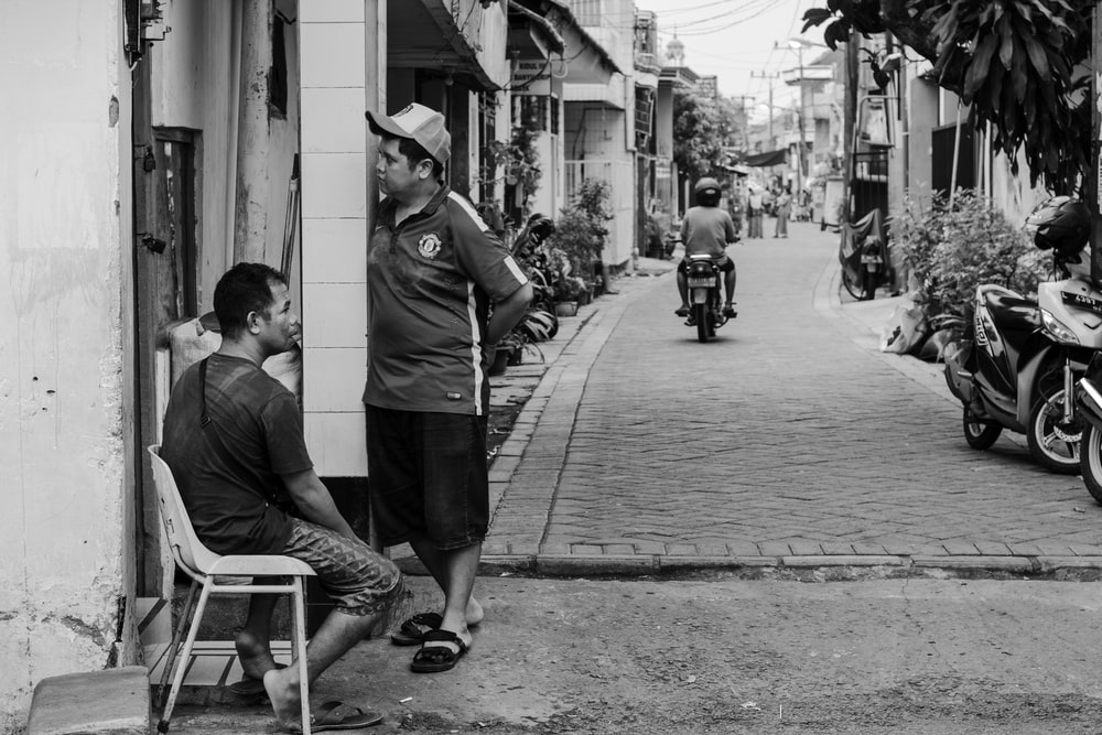 grayscale photography of man sitting on chair beside standing man