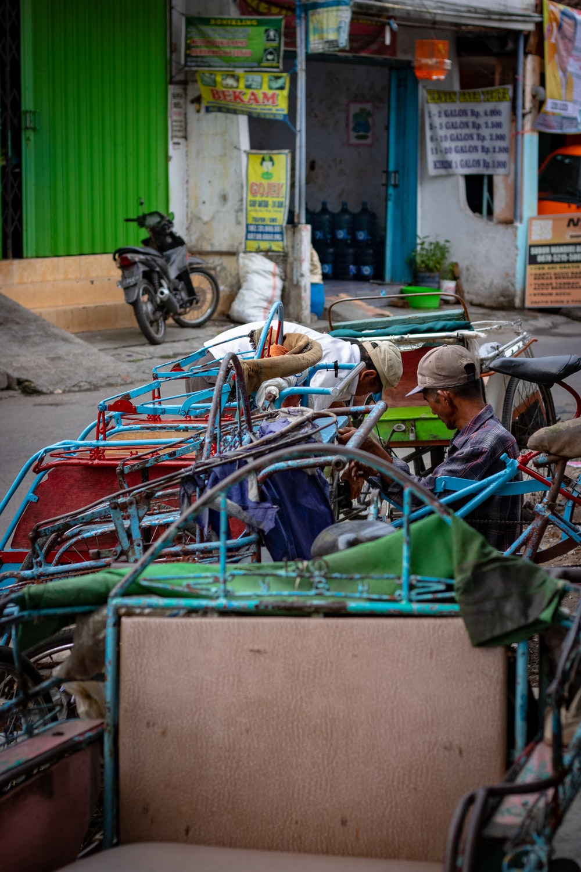 man sitting on pedal trike near buildings