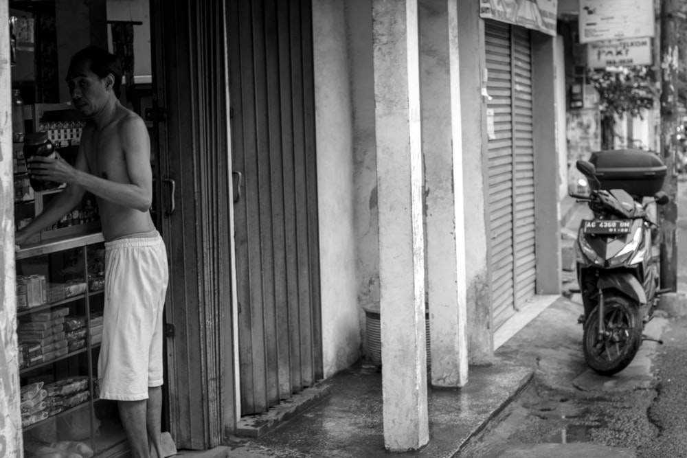 grayscale photography of half naked man at store