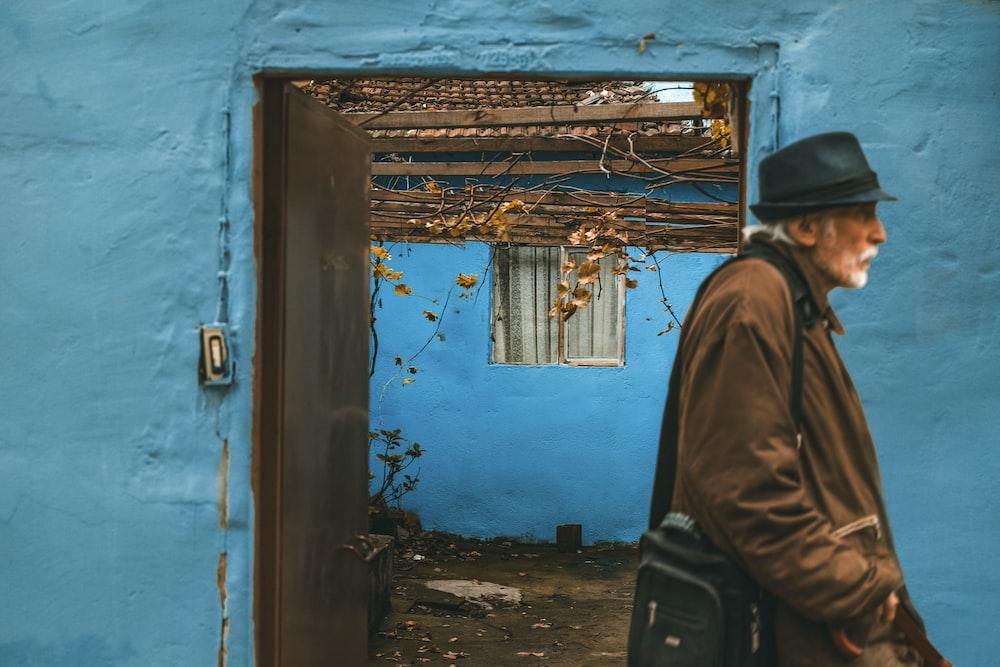 man walking near door painting