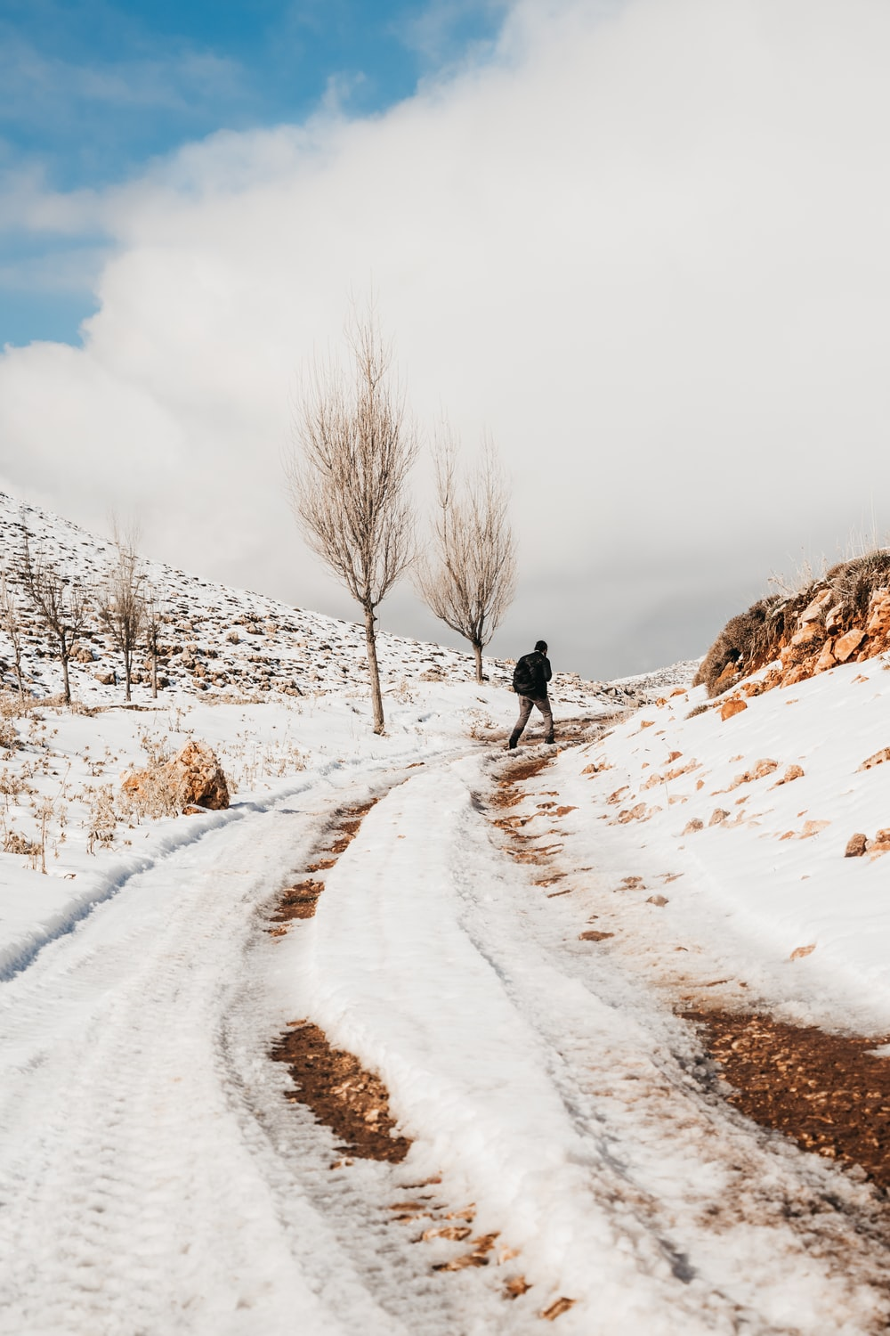 man walking on snow covered road during daytime