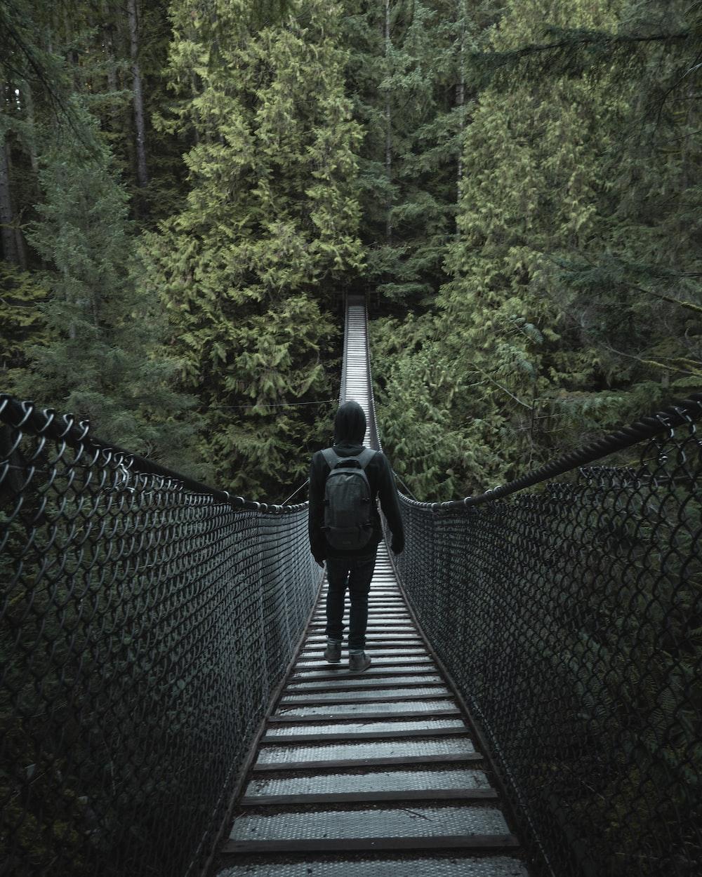 person walking on hanging bridge during daytime