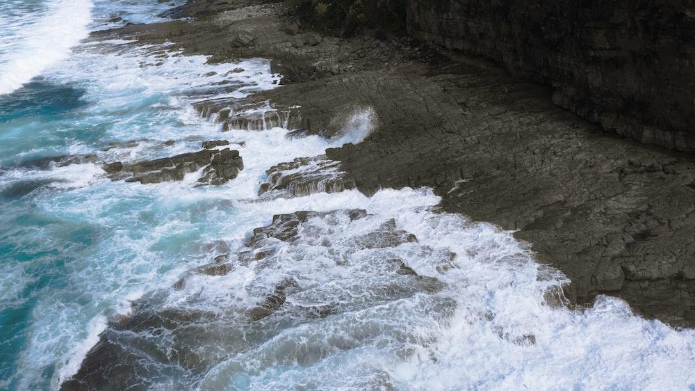 seashore rocks crashing on shore