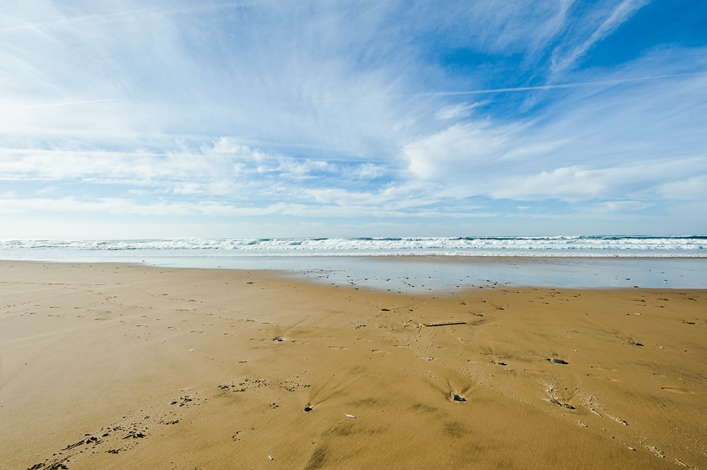 brown sand and body of water under blue sky