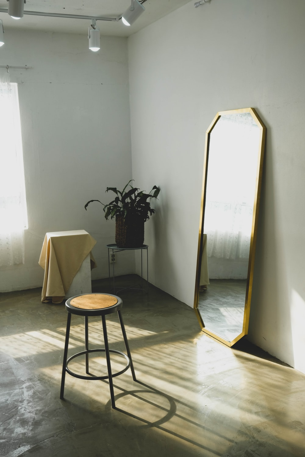 round brown wooden stool near leaning mirror