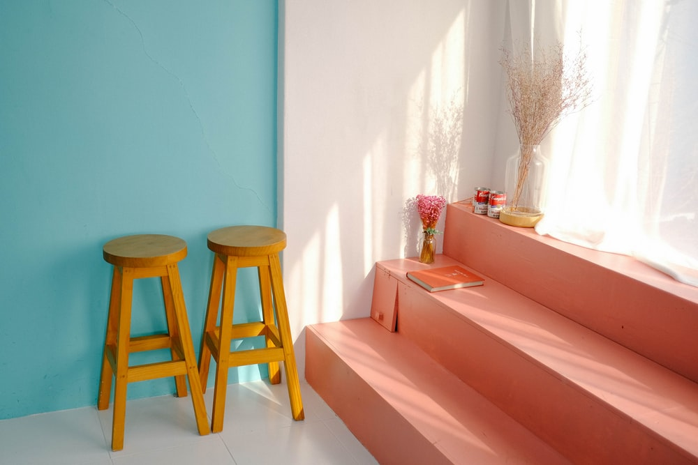 two yellow wooden bar stools