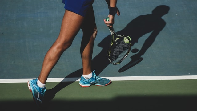 woman holding tennis ball and racket