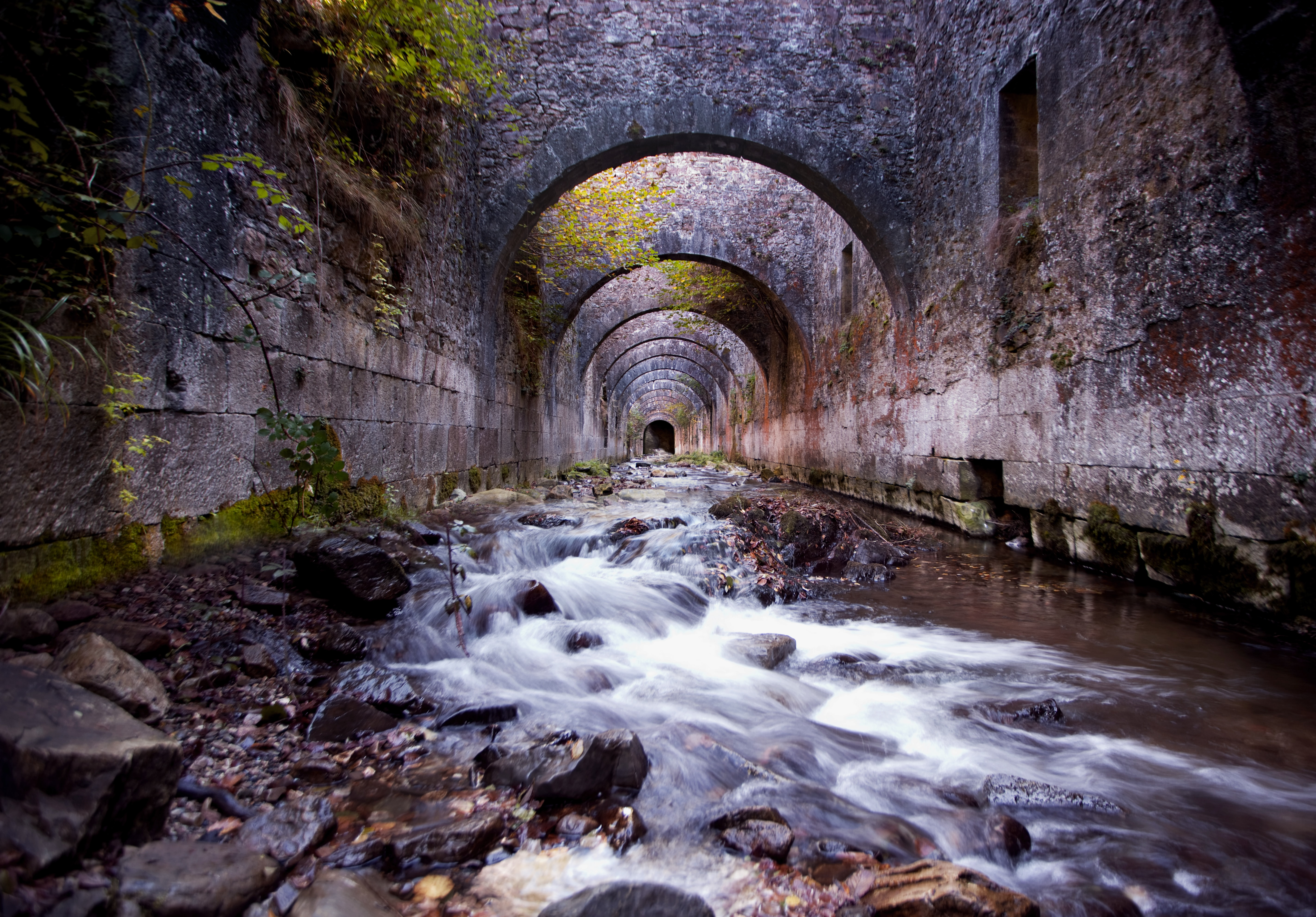 time lapse photography of water flowing on tunnel during daytime