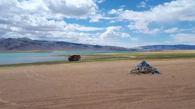 landscape photograph of vehicle near shore mongolia teams background