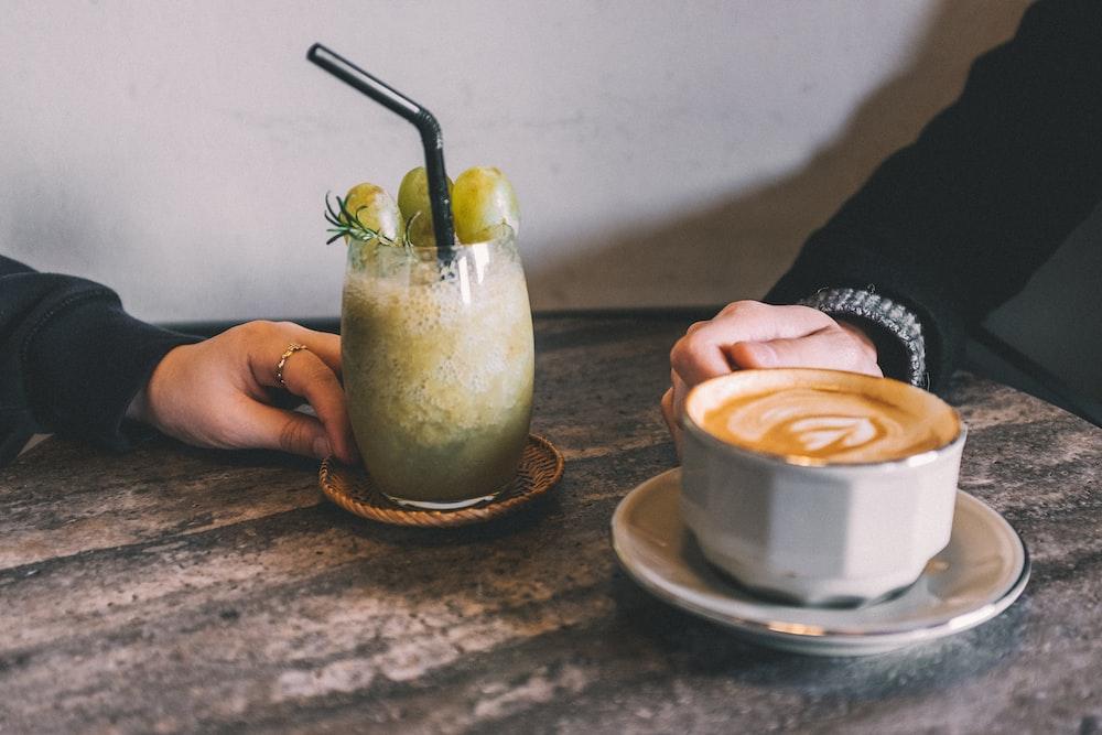 coffee latte beside juice glass