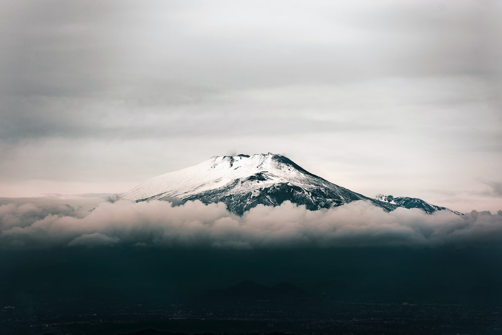 black mountain covered with snow under grey sky