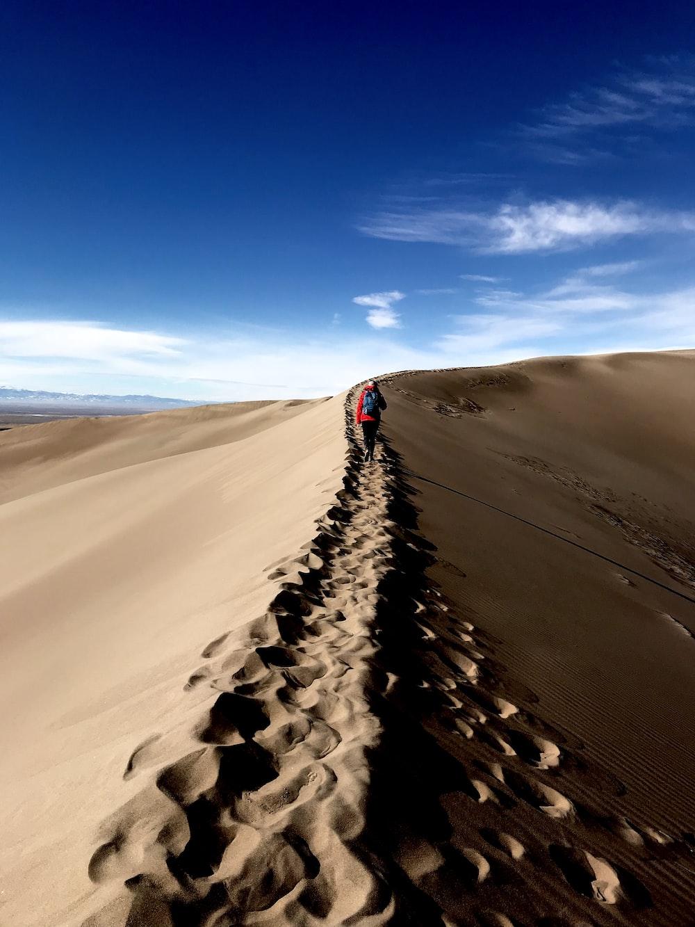 person walking on desert at daytime