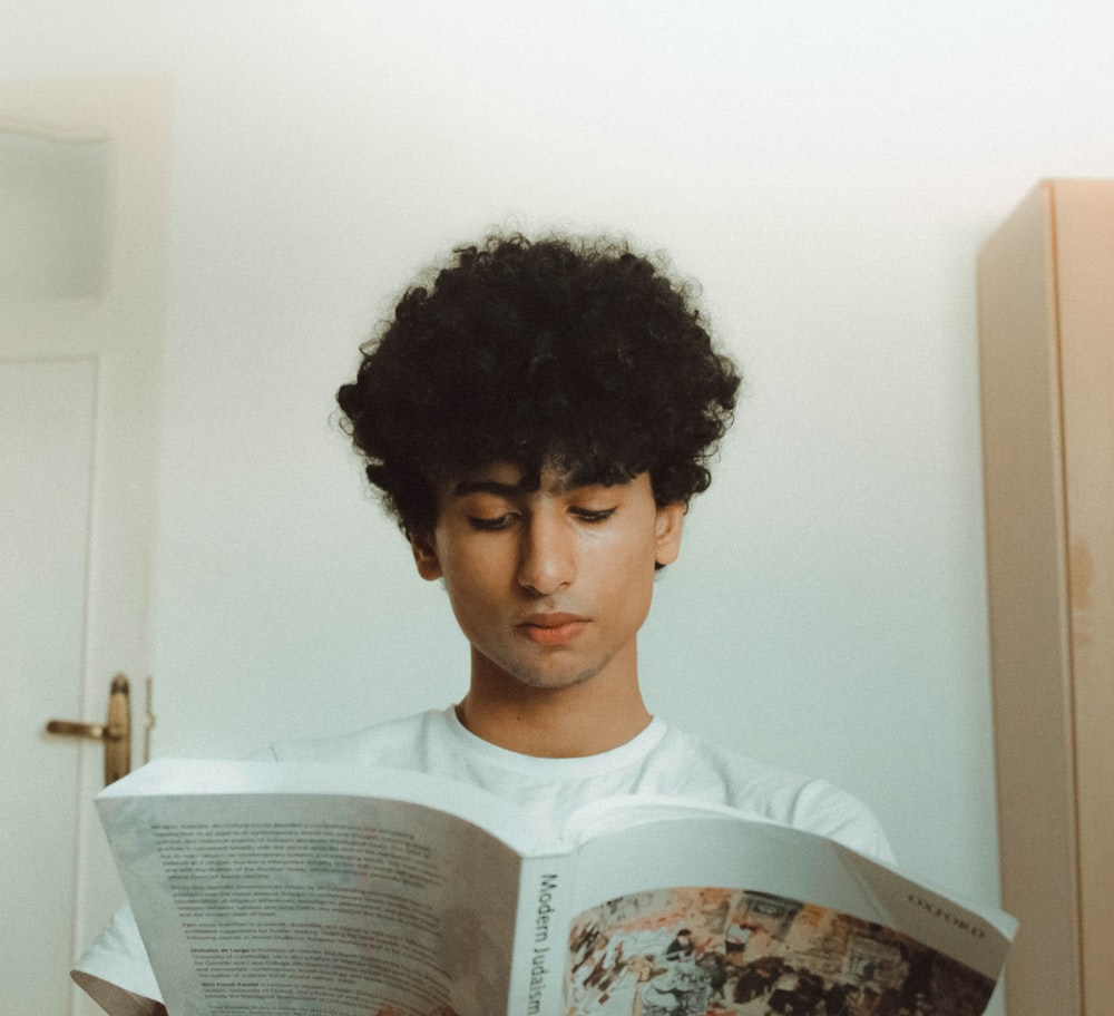 man in white shirt while reading book