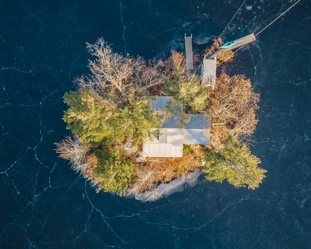 aerial photography of house surrounded by calm water