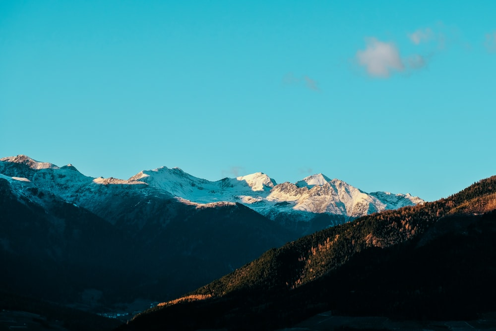snow covered rocky mountain under blue sky