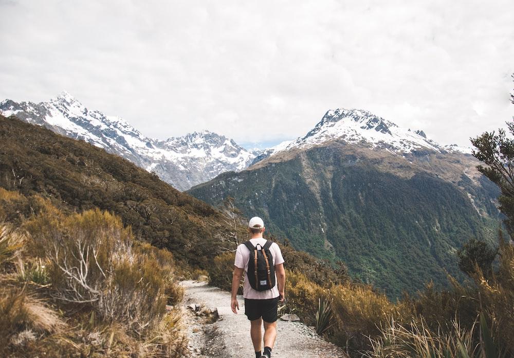 man walking towards mountain during daytime