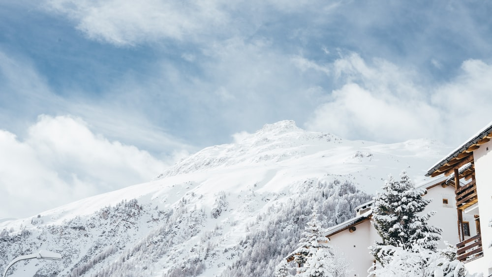 white and brown house and mountain covered snow