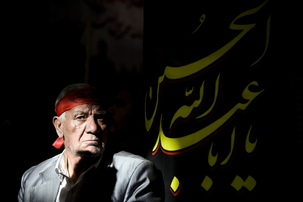 man in black jacket beside a flag with Arabic script text