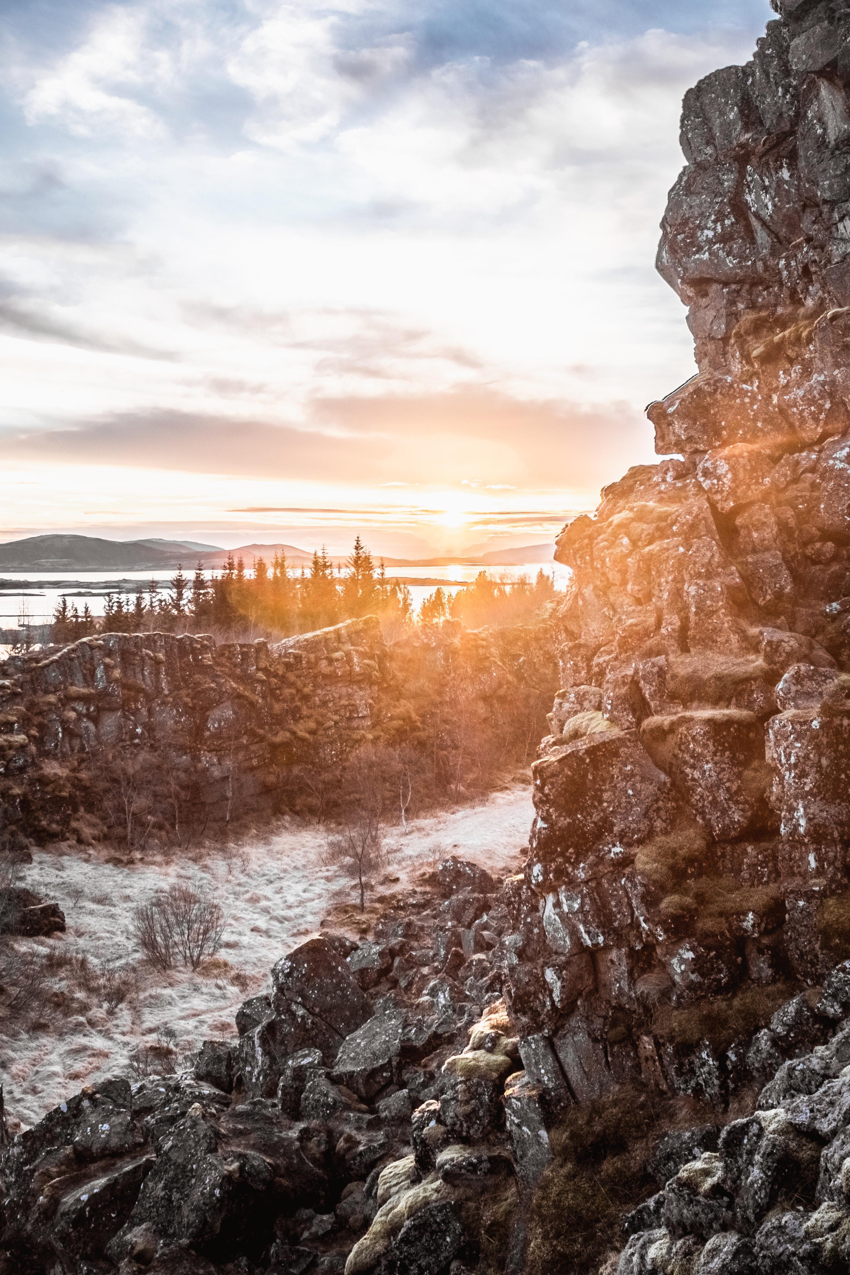 rocky hill beside river across woods aty sunrise