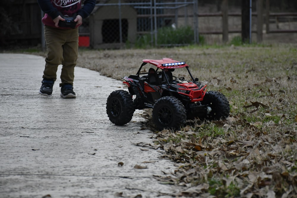 boy controlling red and black R/C UTV toy