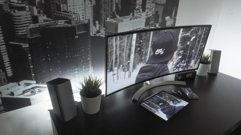 flat screen TV turned on beside white plastic pot