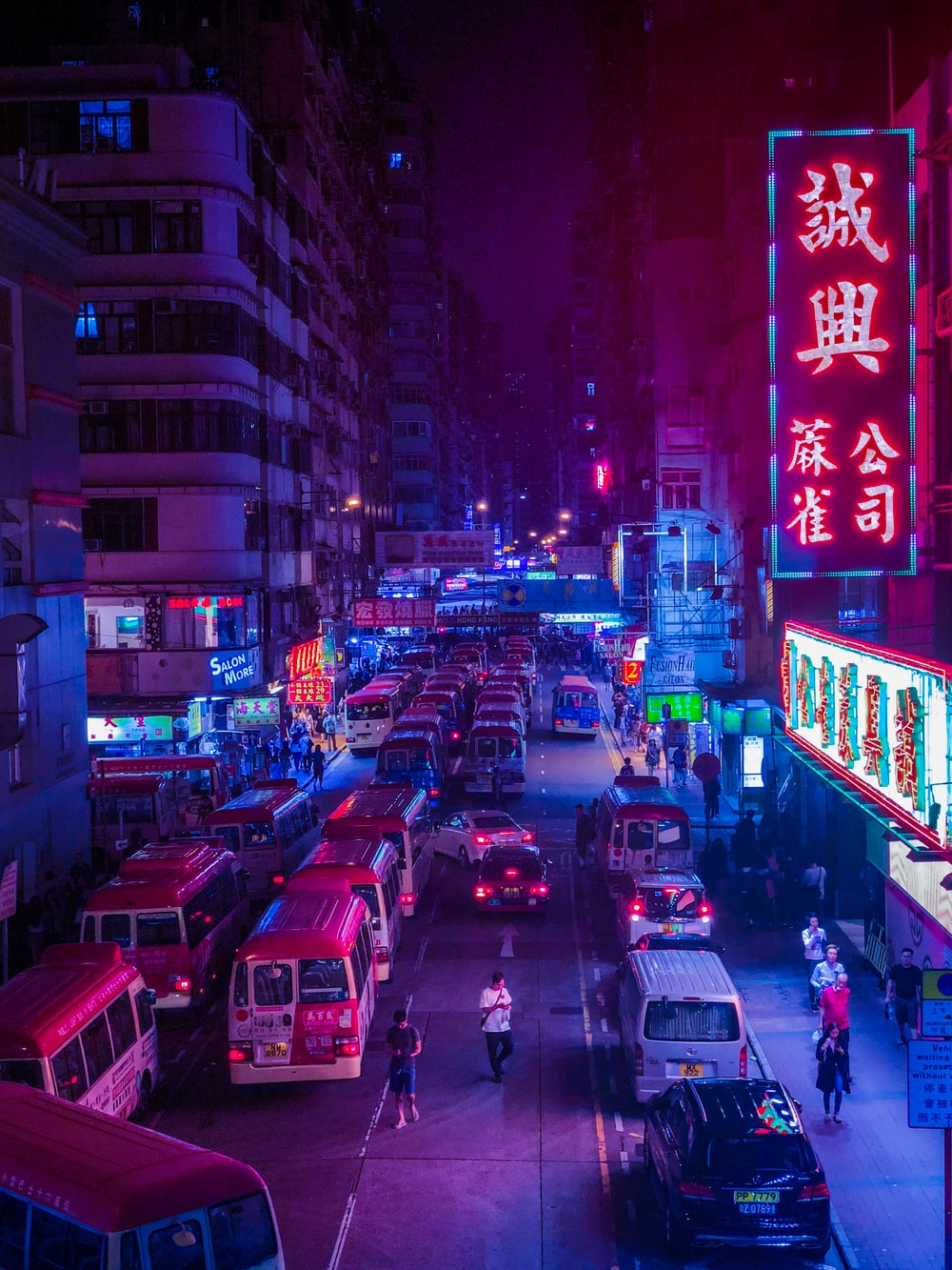 cars on road surrounded by buildings during night time