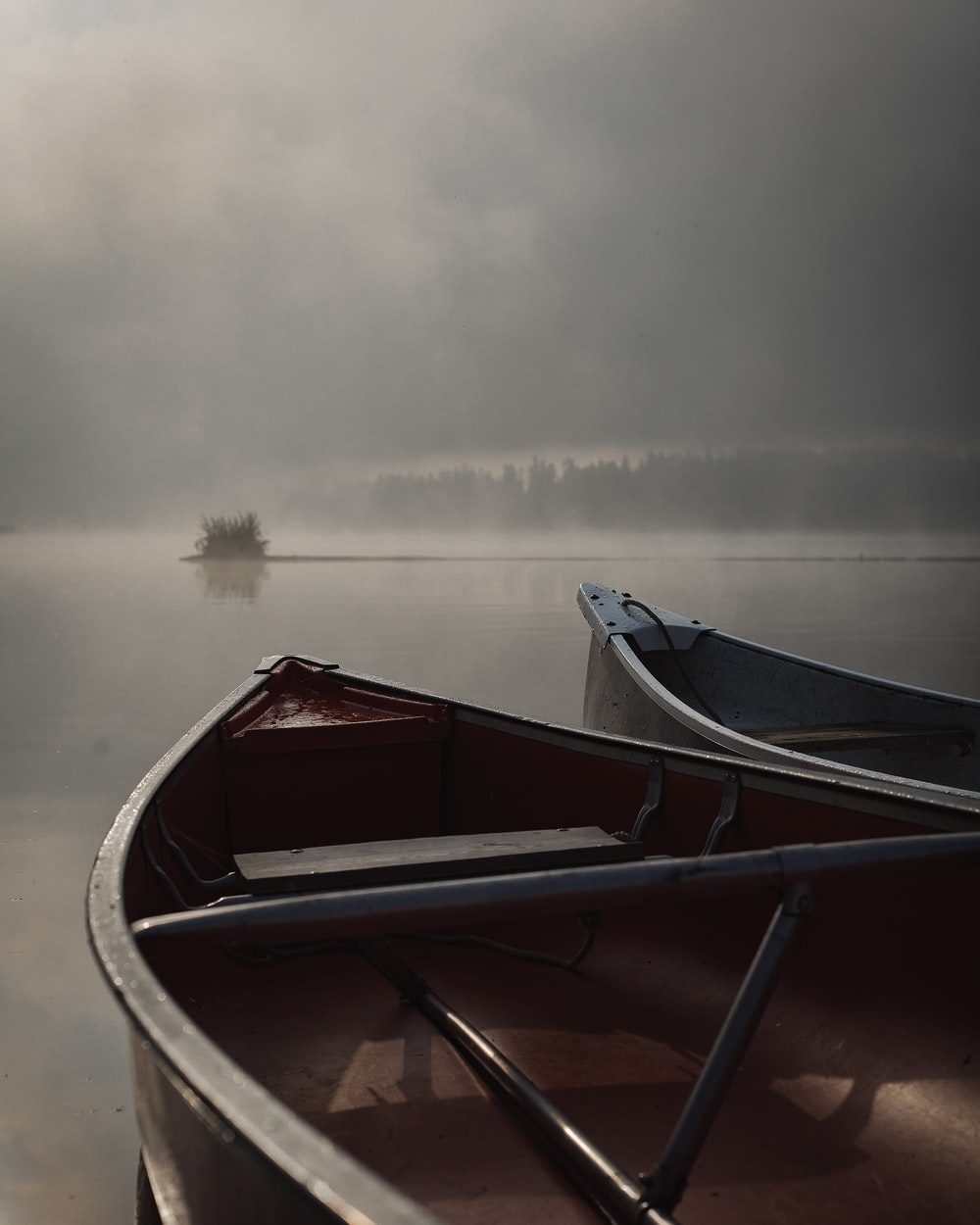boats on body of water during foggy weather