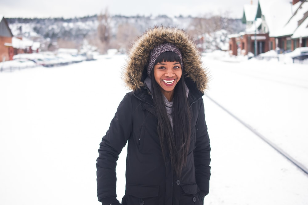 woman wearing coat standing on snow and smiling during daytime