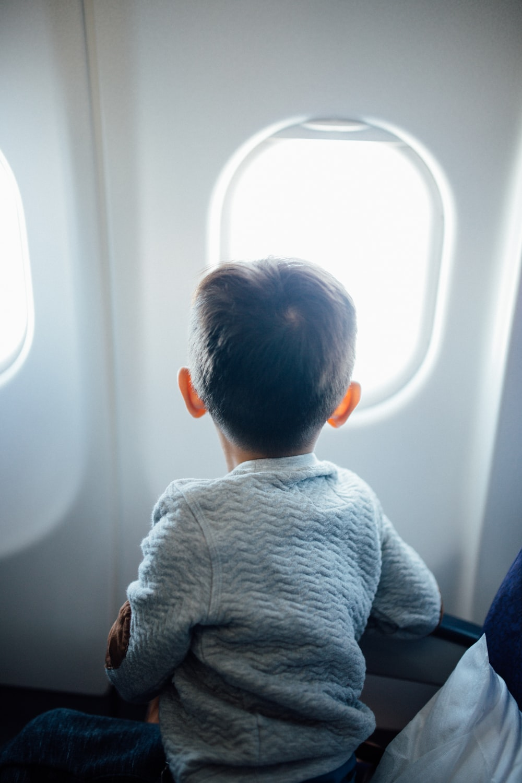 boy sitting on plane seat while viewing window